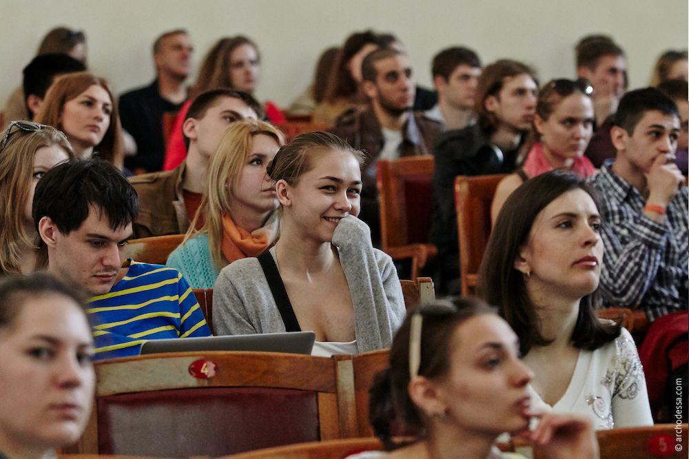 Александр Левицкий слушает речь на английском, посматривает на проектор и обрабатывает фотографии для архитектуры Одессы.