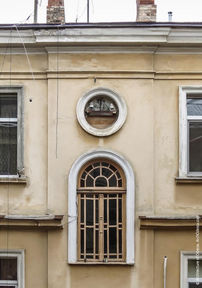Одне з бічних крил, верхнє вікно під'їзду з оригінальною палітуркою
