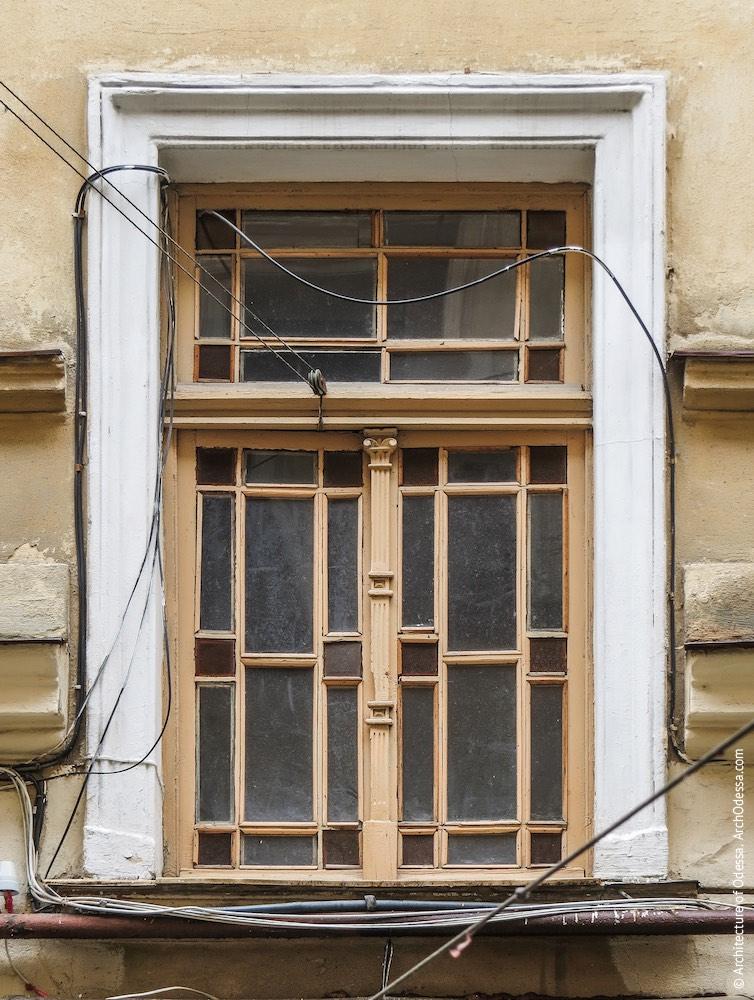 Одне з бічних крил, нижнє вікно під'їзду з оригінальною палітуркою
