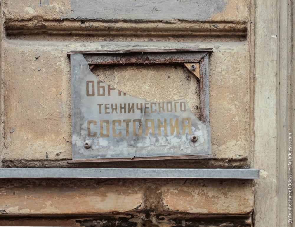 Поврежденная табличка, указывавшая на образцовое некогда техническое состояние дома