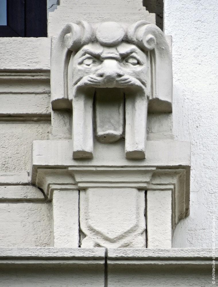 Одна з львиних голів, прикрашають санрик центрального вікна