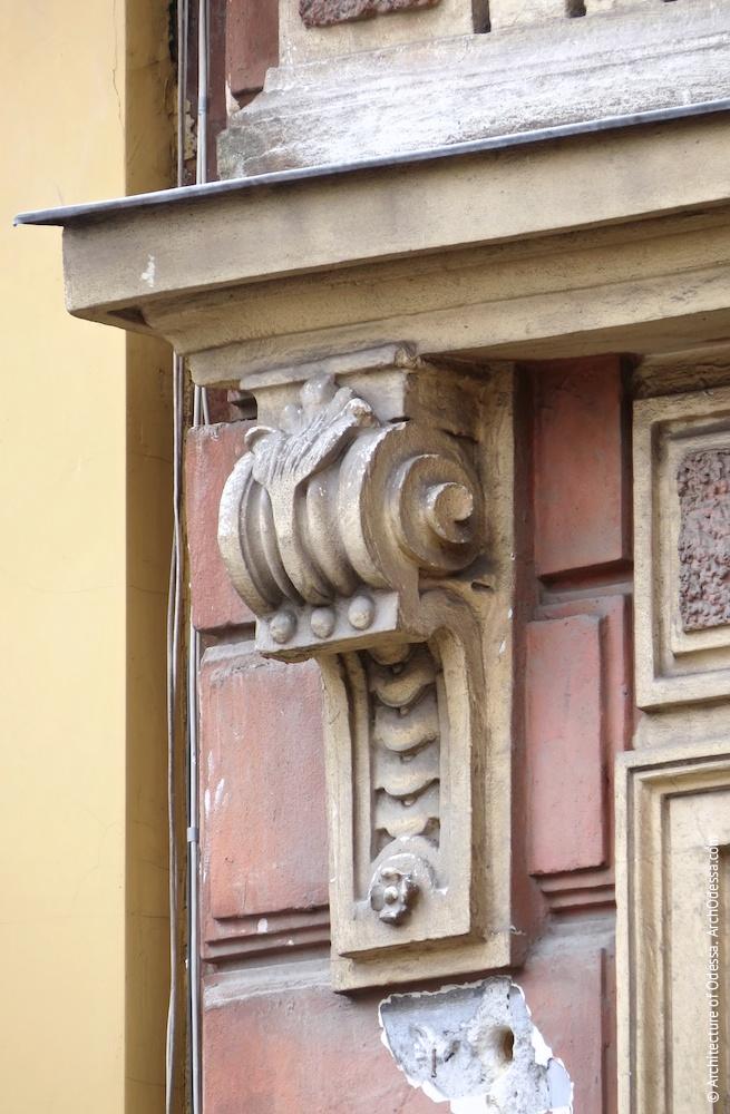 Одна из консолей, фланкирующих филенку над окном второго этажа в  боковом ризалите