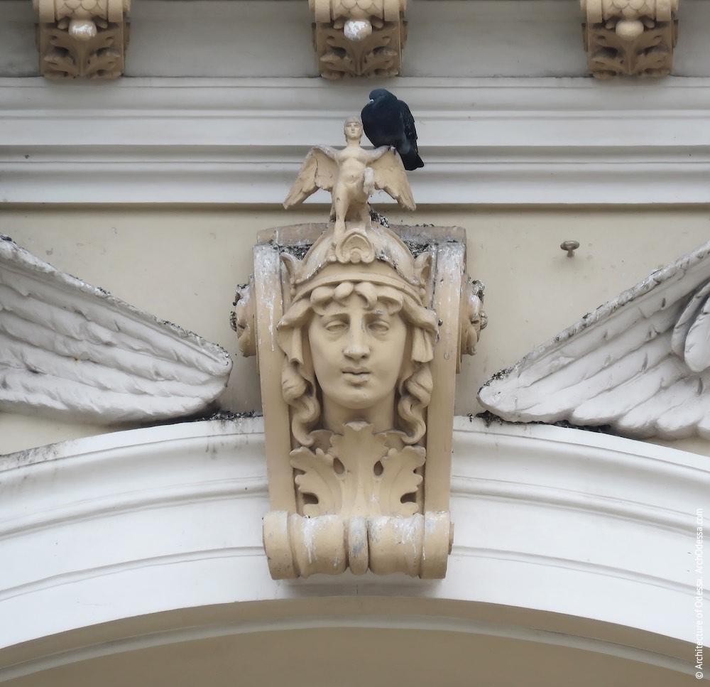 Замковый камень с маскароном над центральным проемом второго яруса