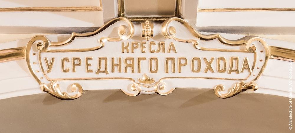 Лепной указатель над центральным проходом в зрительный зал