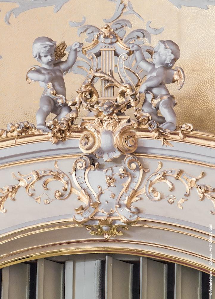 Путти над проемом по центральной оси балконов у сцены
