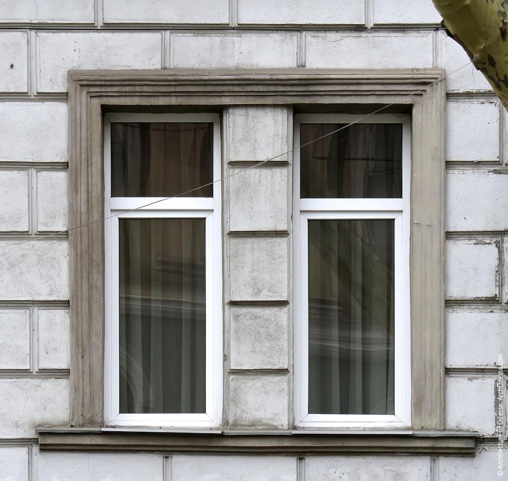 Два сгруппированных окна с общим наличником на первом этаже