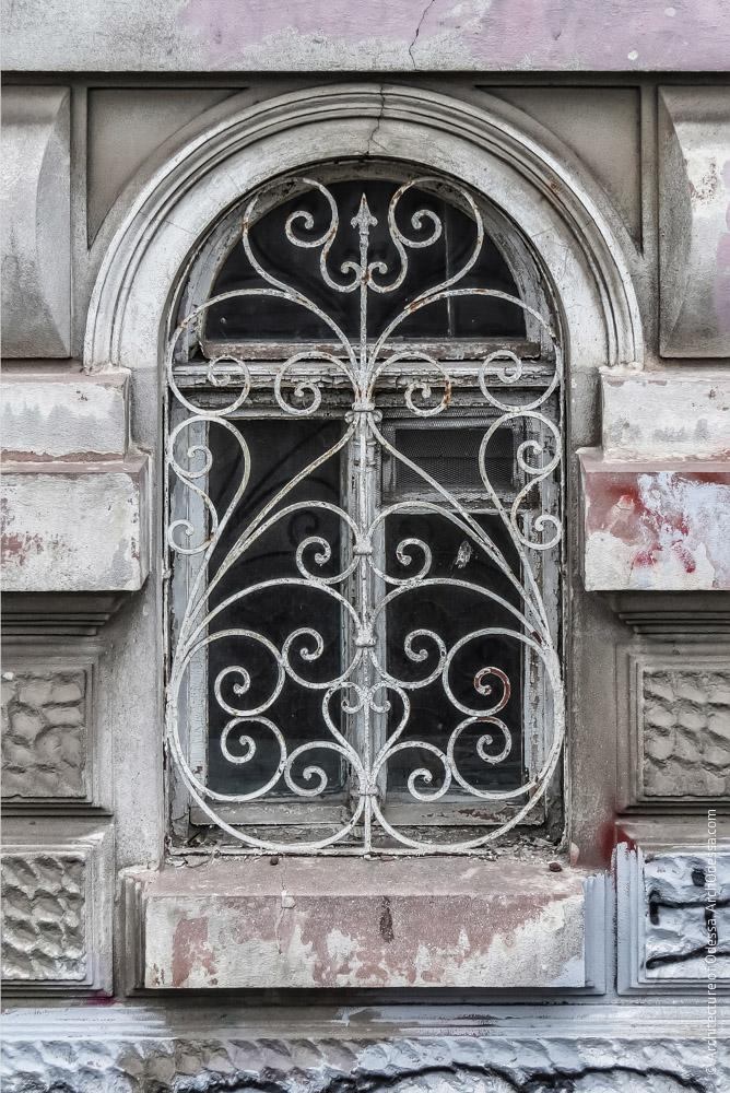 Полуциркульное окно полуподвала и его оригинальная решетка