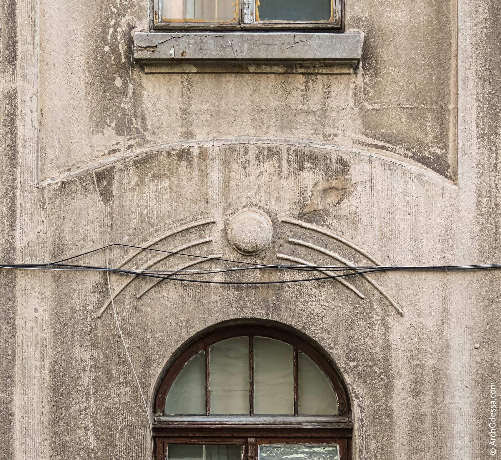 Стилизованный симметричный обрист над окном первого этажа